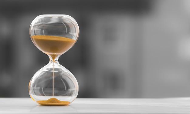 Reloj de arena en un fondo borroso blanco negro. el tiempo es dinero. Foto Premium