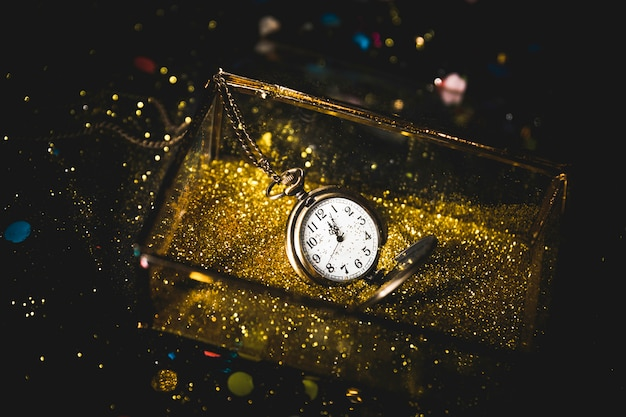 Reloj de bolsillo en caja con lentejuelas. Foto gratis