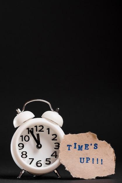 Reloj despertador blanco con texto de tiempo sobre fondo negro Foto gratis