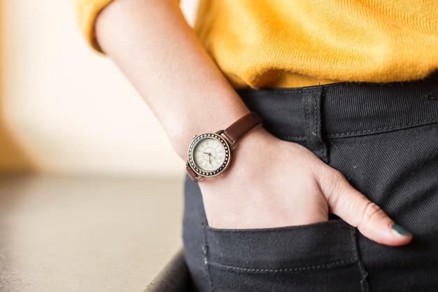 Reloj marrón en la muñeca de una blogger Foto gratis
