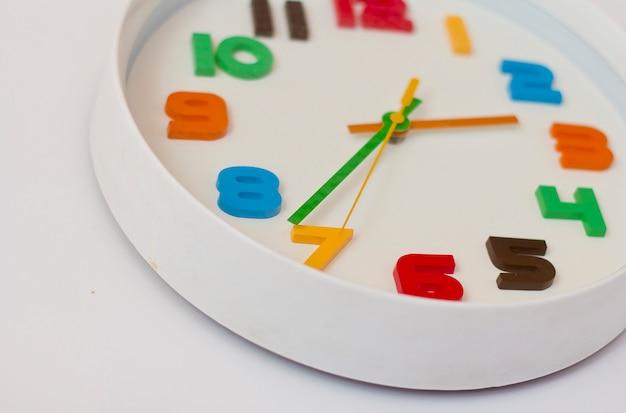 Reloj de pared blanco con números de colores. reloj de