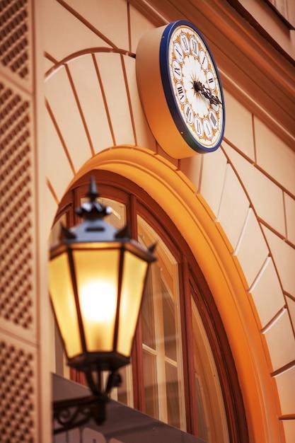 Reloj de pared y farola al atardecer. farolas iluminadas al atardecer. lámparas decorativas. lámpara mágica con una cálida luz amarilla en el crepúsculo de la ciudad. Foto Premium
