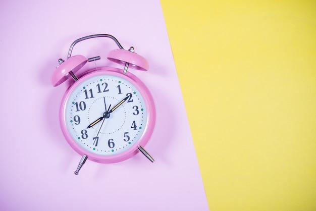 Reloj rosado en el fondo colorido, concepto de la educación Foto gratis
