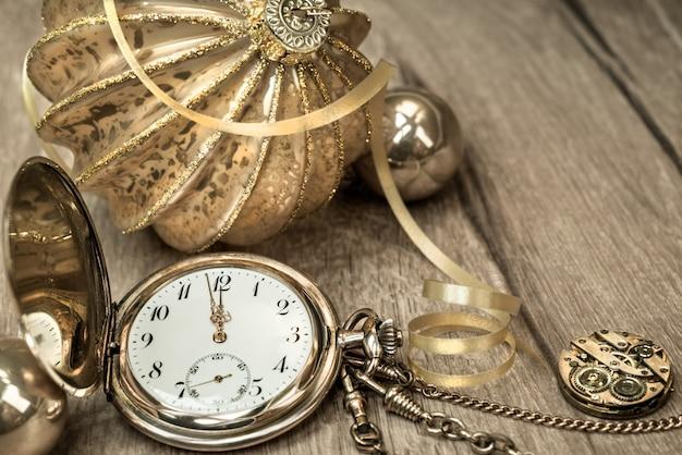 Reloj vintage que muestra de cinco a doce y decoraciones en madera. Foto Premium
