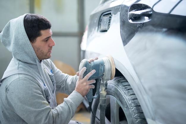 Reparador de automóviles pulido de la carrocería con una máquina que prepara el vehículo para pintar Foto gratis
