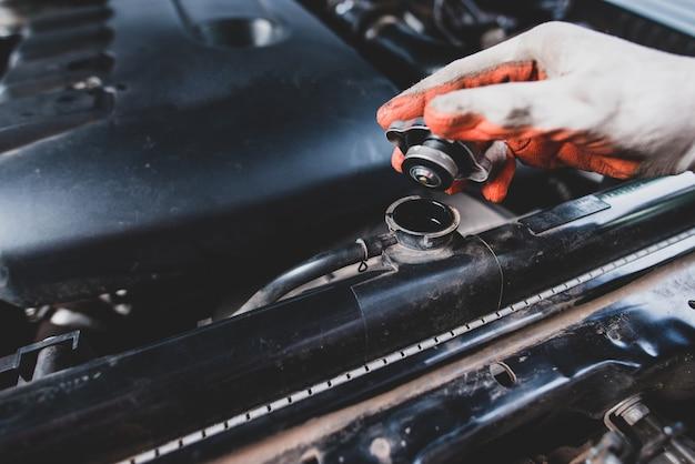Reparador de automóviles con un uniforme blanco de pie y sosteniendo una llave que es una herramienta esencial para un mecánico Foto gratis