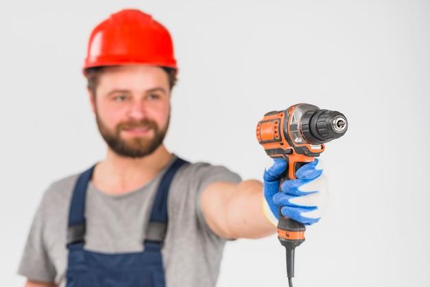 Reparador que sostiene el taladro en la mano Foto gratis