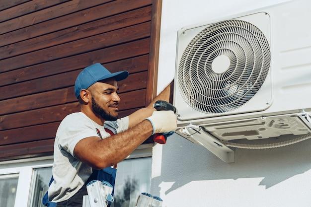 Reparador en uniforme instalando la unidad exterior de aire