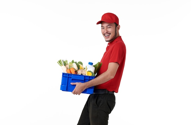 Repartidor asiático vistiendo uniforme rojo con canasta de comida fresca aislada sobre pared blanca. Foto gratis