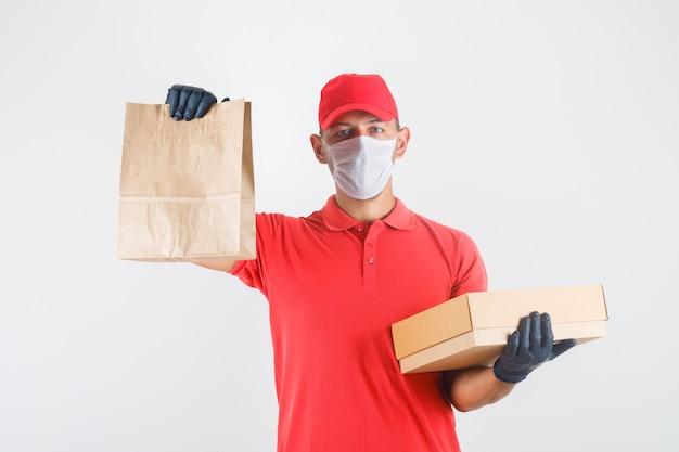 Repartidor con bolsa de papel y caja de cartón en uniforme rojo, máscara médica, guantes vista frontal. Foto gratis