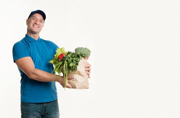 Repartidor con bolsa de supermercado con espacio de copia Foto gratis