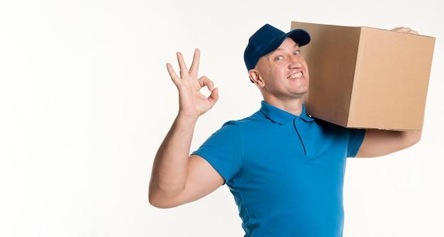 Repartidor con caja de cartón en el hombro y signo bien Foto gratis