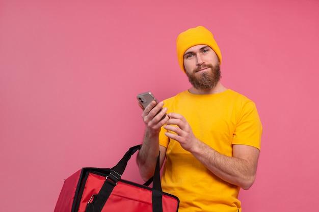 Repartidor europeo alegre con teléfono de espera casual de bolso en rosa Foto gratis