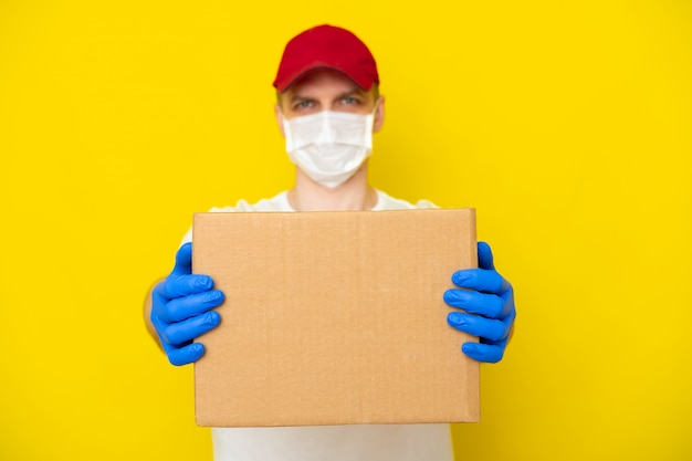 Repartidor de gorra roja camiseta blanca uniforme cara máscara médica guantes mantenga caja de cartón vacía en la pared amarilla. servicio de coronavirus. las compras en línea. bosquejo Foto Premium