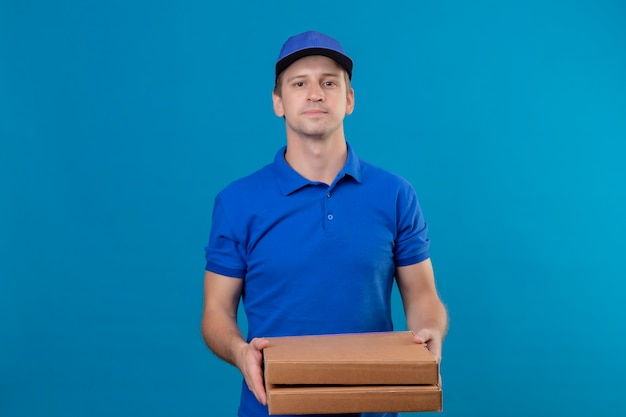 Repartidor guapo joven en uniforme azul y gorra sosteniendo cajas de pizza con expresión de confianza en la cara de pie sobre la pared azul Foto gratis