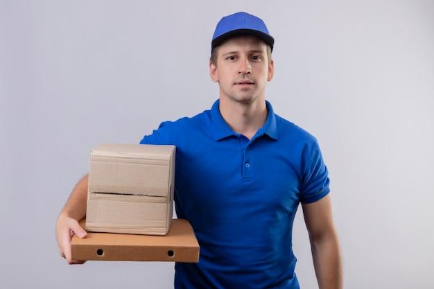 Repartidor guapo joven en uniforme azul y gorra sosteniendo cajas de pizza con expresión de confianza en la cara de pie sobre la pared blanca Foto gratis