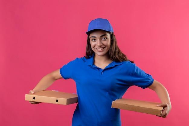 Repartidor joven en uniforme azul y gorra sosteniendo cajas de pizza mirando a la cámara sonriendo confiada feliz y positiva de pie sobre fondo rosa Foto gratis