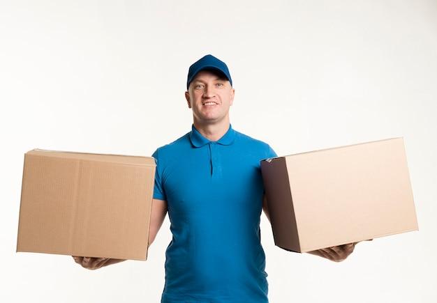 Repartidor posando con cajas de cartón en cada mano Foto gratis