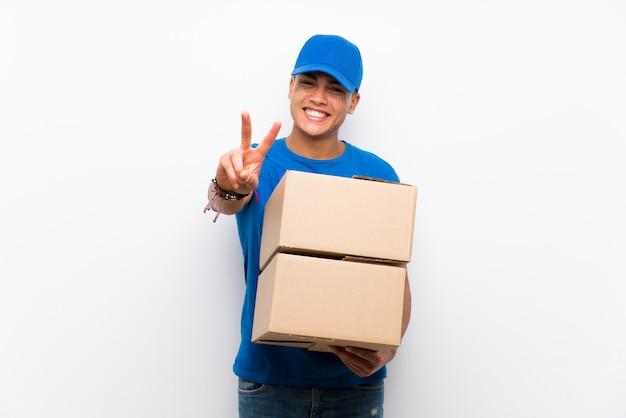 Repartidor sobre pared blanca aislada sonriendo y mostrando el signo de la victoria Foto Premium