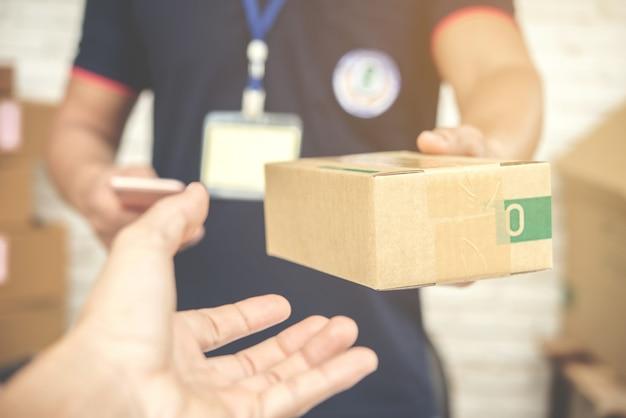 Repartidor sonriendo y sosteniendo una caja de cartón Foto gratis