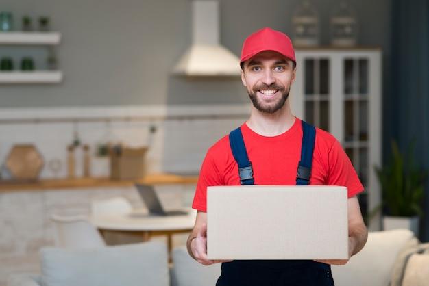 Repartidor sonriente posando mientras sostiene la caja Foto gratis