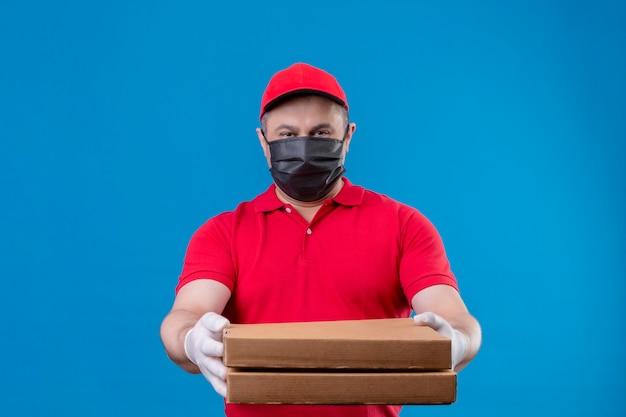 Repartidor vestido con uniforme rojo y gorra en máscara protectora facial sosteniendo cajas de pizza que se extienden a la cámara mirando confiado de pie sobre el espacio azul Foto gratis