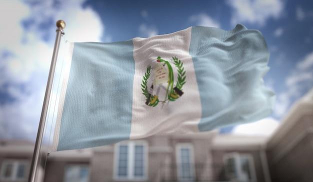 Representación de la bandera de guatemala 3d en el fondo del edificio del cielo azul Foto Premium