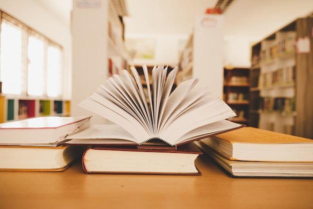 Reserve en la biblioteca con el viejo libro de texto abierto, apile pilas de archivos de texto de literatura en el escritorio de lectura Foto gratis