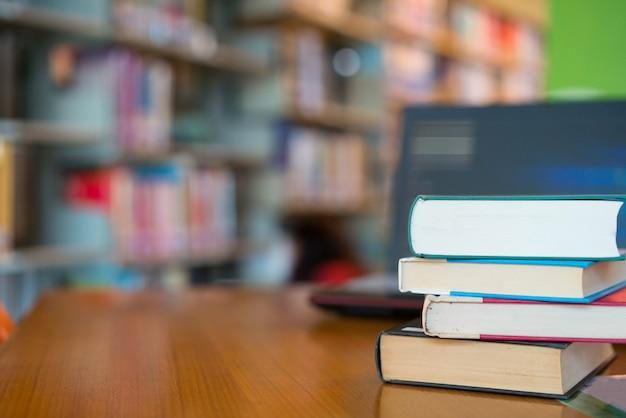 Reserve en la biblioteca con un viejo libro de texto abierto, apile pilas de archivos de texto de literatura en la mesa de lectura Foto Premium