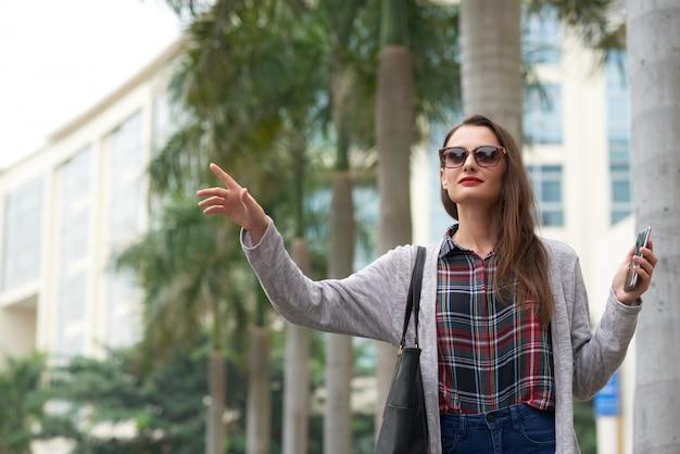 Residente urbano femenino tomando taxi en el centro Foto gratis