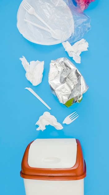 Residuos de basura plástica cerca de bin sobre fondo azul. Foto gratis