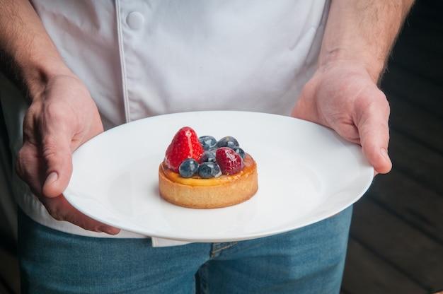 Restaurante chef sosteniendo plato con postre dulce Foto gratis