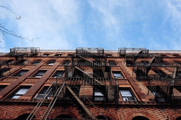 Resultado de ángulo bajo de un complejo de apartamentos con escalera de emergencia de metal en el lateral Foto gratis