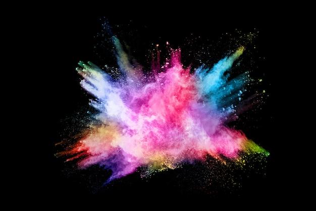 Resumen explosión de polvo coloreado sobre un fondo negro Foto Premium