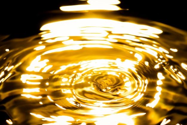 Resumen de metal dorado líquido, gotas de agua olas y ondas Foto Premium
