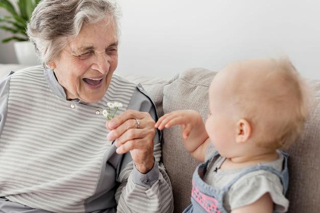Retrato de abuela feliz jugando con bebé Foto Premium