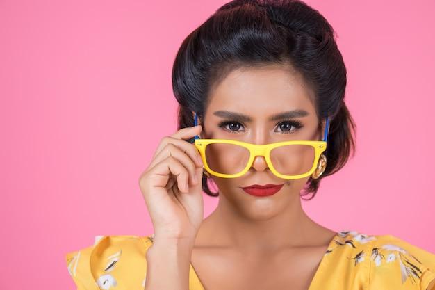 Retrato de acción de mujer de moda con gafas de sol. Foto gratis