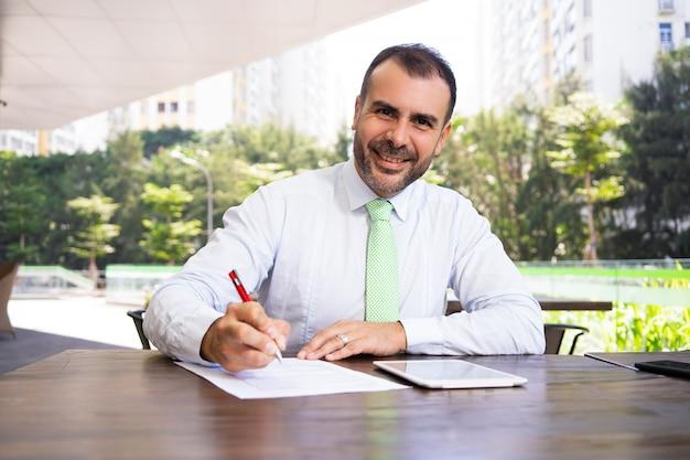 Retrato del acuerdo de firma sonriente del hombre de negocios maduro al aire libre Foto gratis