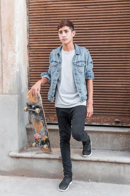 Retrato de un adolescente parado frente a un revestimiento de hierro corrugado cerrado con una tabla de skate Foto gratis