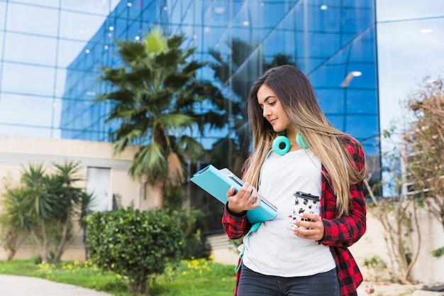 Retrato de una adolescente que mira la pila de libros y la taza de café para llevar contra el edificio de la universidad Foto gratis