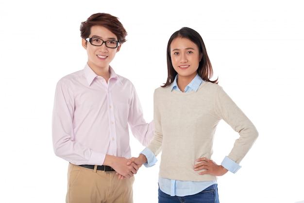 Retrato de adolescentes asiáticos estrechándose las manos de pie Foto gratis