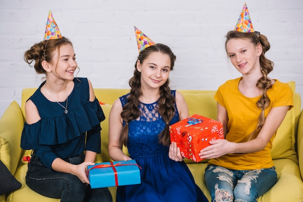Retrato de adolescentes felices que se sientan en el sofá amarillo con sus amigos que llevan a cabo presentes Foto gratis
