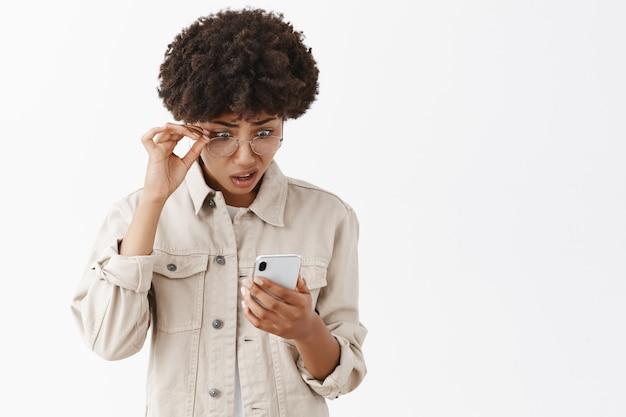 Retrato de afroamericana intensa confundida y cuestionada no puede creer en tonterías que leyó a través de smarpthone, quitándose las gafas, haciendo muecas, mirando con estupor a la pantalla Foto gratis