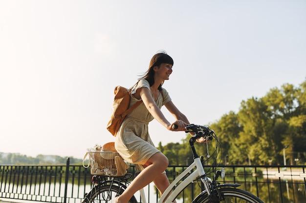 Retrato al aire libre de la atractiva joven morena con un sombrero en una bicicleta. Foto gratis