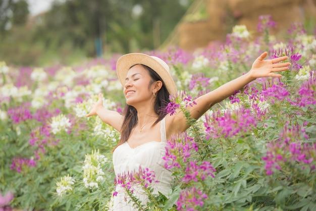 Retrato al aire libre de una hermosa mujer de mediana edad de asia. chica atractiva en un campo con flores Foto gratis