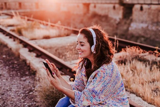 Retrato al aire libre de una joven bella mujer al atardecer escuchando música en auriculares y sonriendo Foto Premium