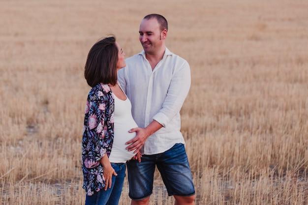 Retrato al aire libre de una joven pareja embarazada caminando por un campo amarillo. estilo de vida familiar al aire libre. Foto Premium