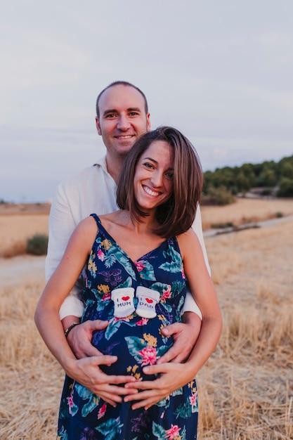 Retrato al aire libre de una joven pareja embarazada en un campo amarillo. estilo de vida familiar al aire libre. sosteniendo calcetines con el mensaje i love mum, i love dad Foto Premium