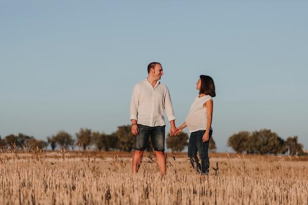Retrato al aire libre de una joven pareja joven embarazada en un campo amarillo. estilo de vida familiar al aire libre. Foto Premium