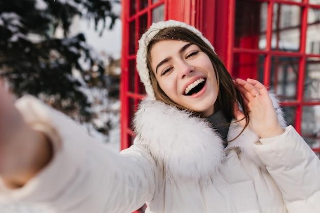 Retrato al aire libre de linda mujer con sonrisa feliz haciendo selfie en londres durante las vacaciones de invierno. adorable mujer con sombrero blanco tomando fotos de herslef junto a la cabina de teléfono roja. Foto gratis